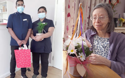 Two staff members with their leaving presents and a resident creating a May Day maypole flower arrangement at Abbotsleigh Care Home